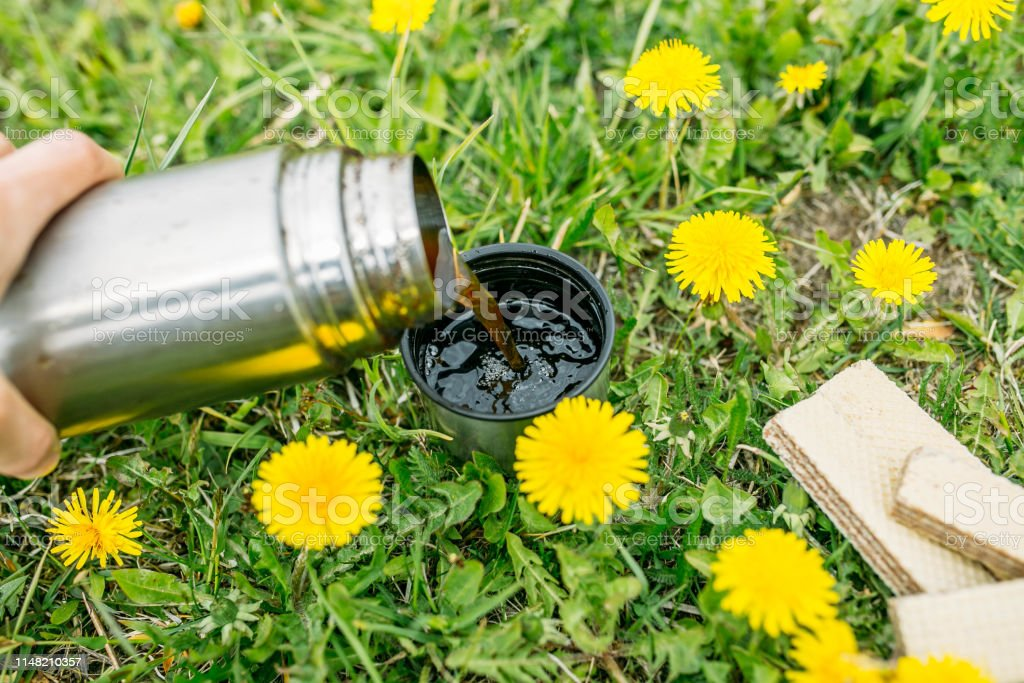 picnic in the summer, coffee tea from a thermos among the yellow...