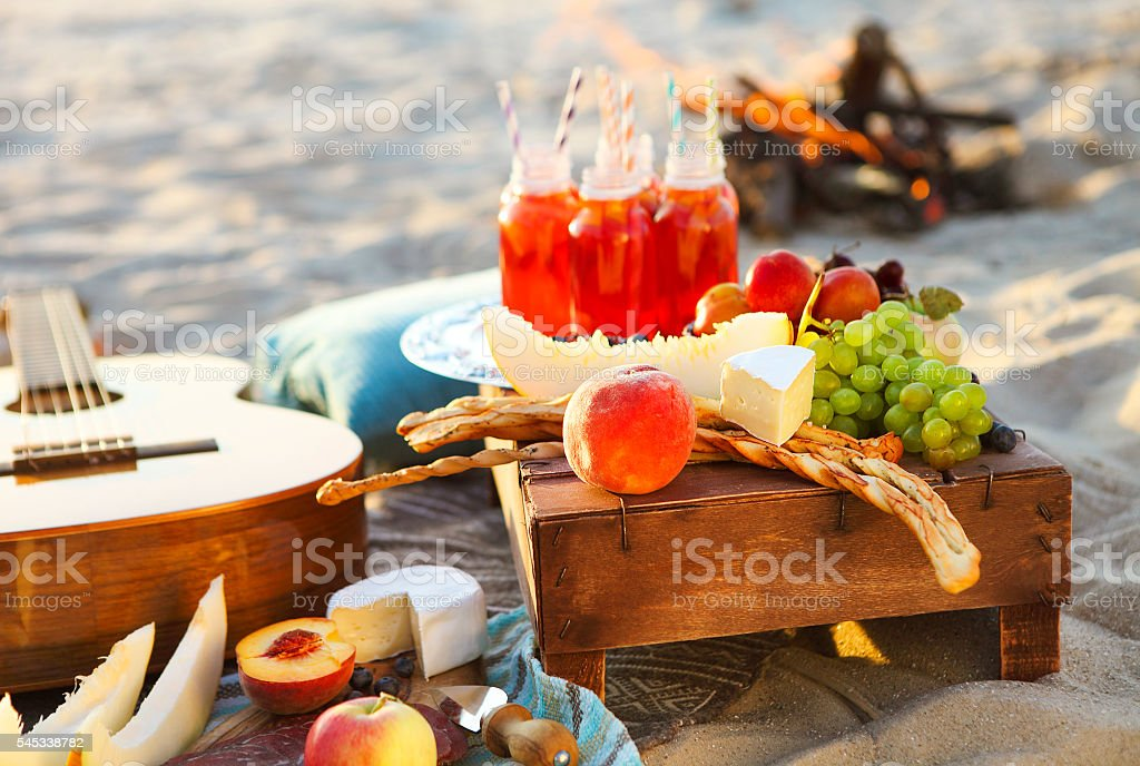 Picnic on the beach at sunset with fruits and juices stock photo