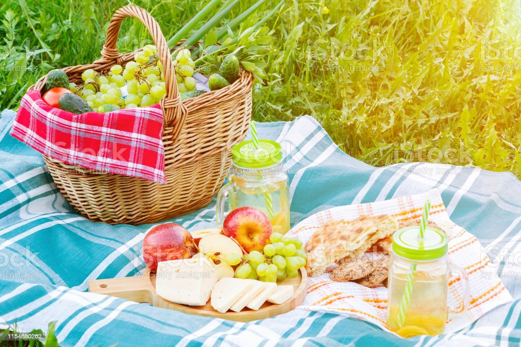 Picnic on the grass on a summer day - basket, grapes, cheese, bread,...