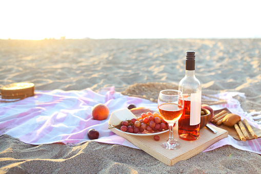 Picnic outdoor with rose wine fruits meat and cheese