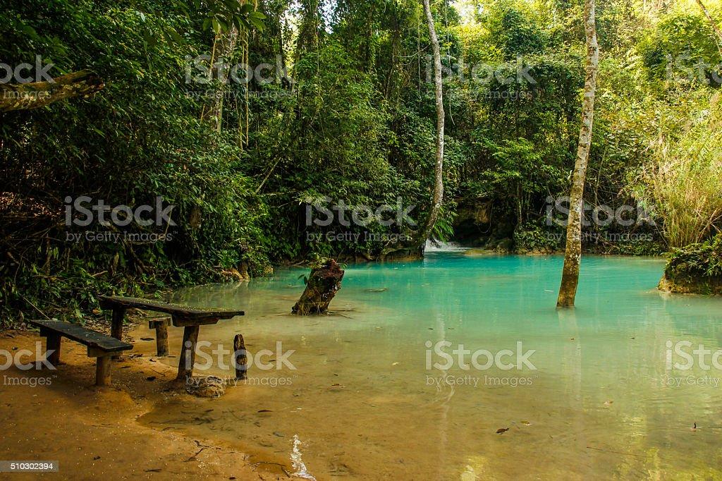 Picnic table at Kuang Si waterfalls stock photo