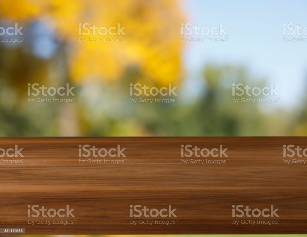 Picnic table, natural  woodgrain texture. Ideal to position products on and place in the foreground of any image.  Selective focus. Very shallow depth of field for soft background.  Autumn forest in the background. royalty-free stock photo
