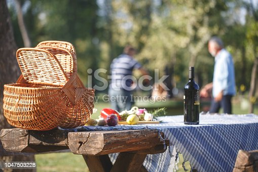 Food on the table during picnic day and people in the background near the barbeque.