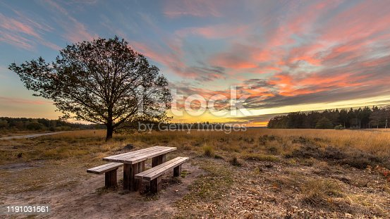 Picnic table in heathland nature reserve under beautif sunset with orange and pink clouds in Drenthe, Netherlands.