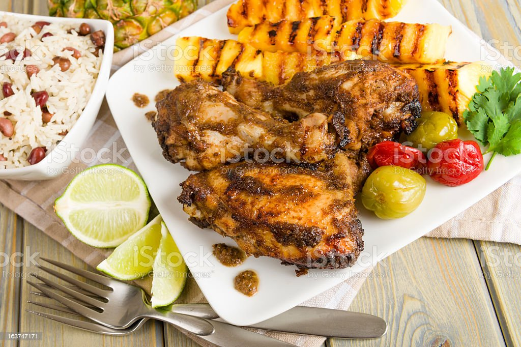 Picnic table with barbecue chicken, peppers, rice, and lemon stock photo