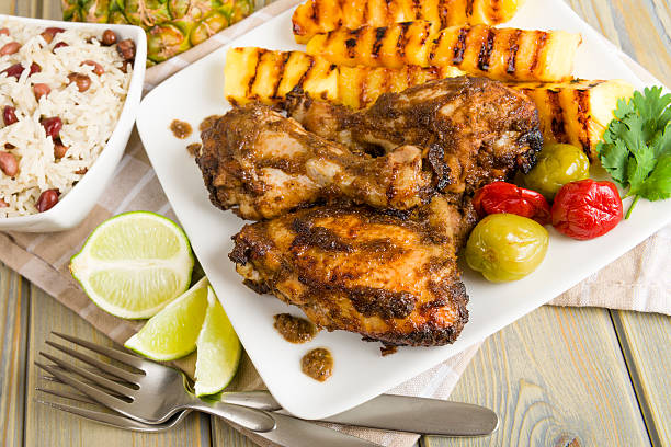 picnic table with barbecue chicken, peppers, rice, and lemon - caribbean culture stock pictures, royalty-free photos & images