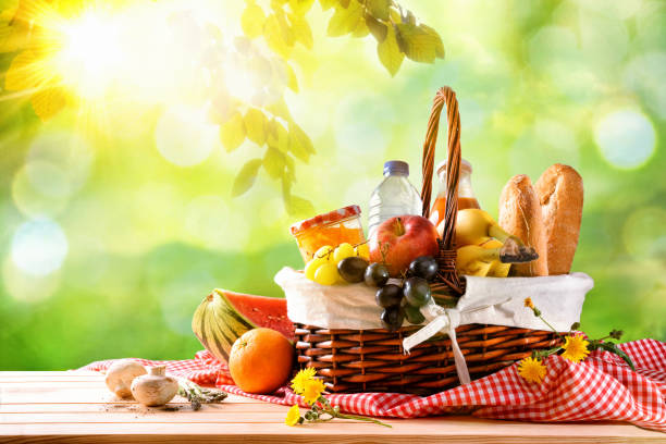 Picnic wicker basket with food on table in the field stock photo