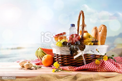istock Picnic wicker basket with food on table on the beach 689004422