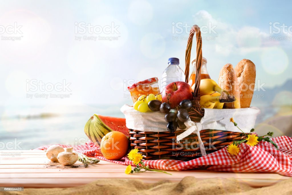 Picnic wicker basket with food on table on the beach stock photo