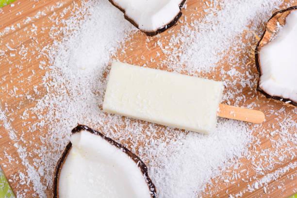 Picolé de Coco Picolé de Coco em uma mesa com pedaços de coco ice cream bar stock pictures, royalty-free photos & images