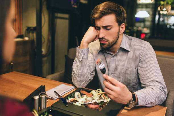 pictue of guy sitting together with his girlfriend and eating some food they have ordered. man has found some meat on the plate. he is looking to the piece of meat with suspicious sight. - slow food foto e immagini stock