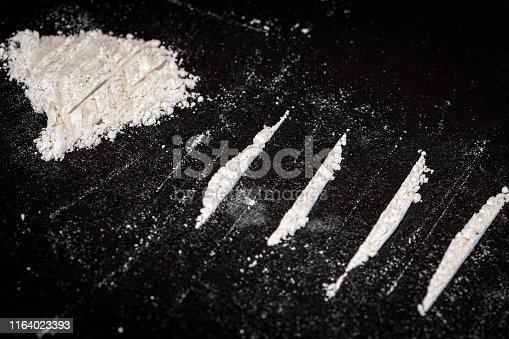 Representation of the abusive consumption of drugs, a lot of cocaine and some white lines and a banknote in the background on a black background