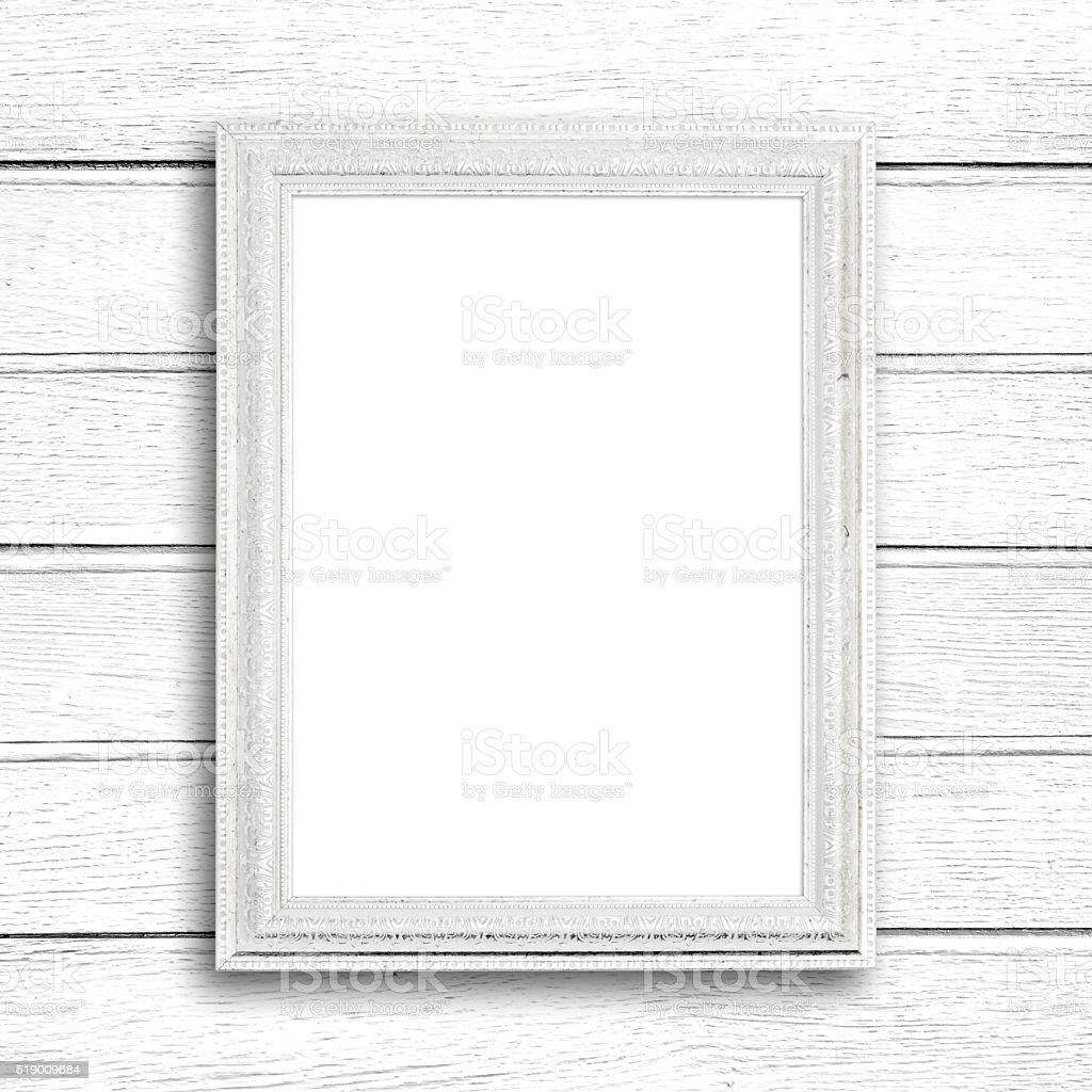 White picture frame on white wood wall.