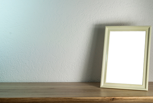 a empty white picture frame on a desk.