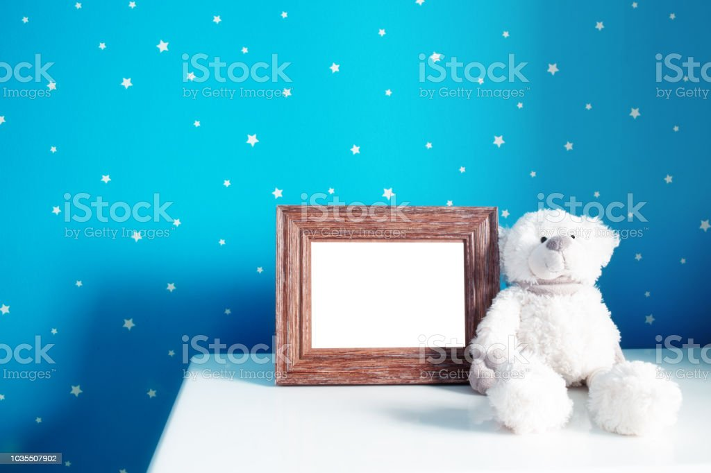 Picture frame with teddy bear in beautiful baby room stock photo