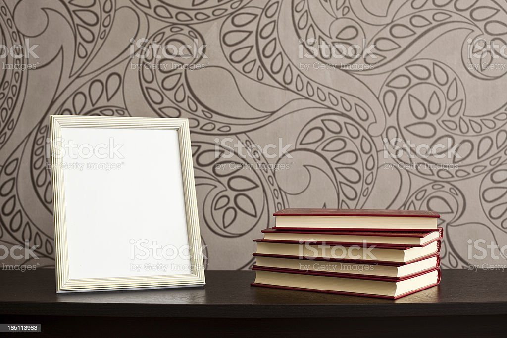 Picture frames and books on desk with floral wallpaper background royalty-free stock photo