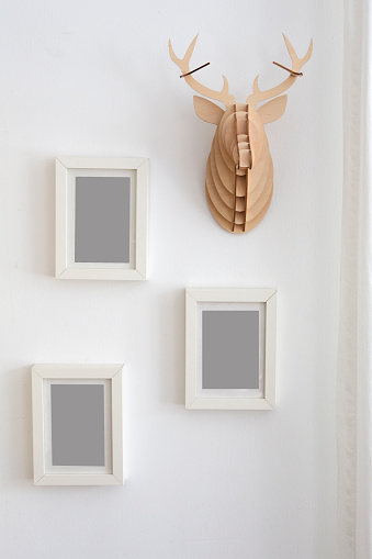 three empty picture frames on wall next to decorative fake antler