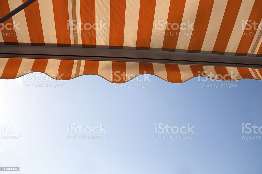 A picture looking upwards at a striped awning stock photo