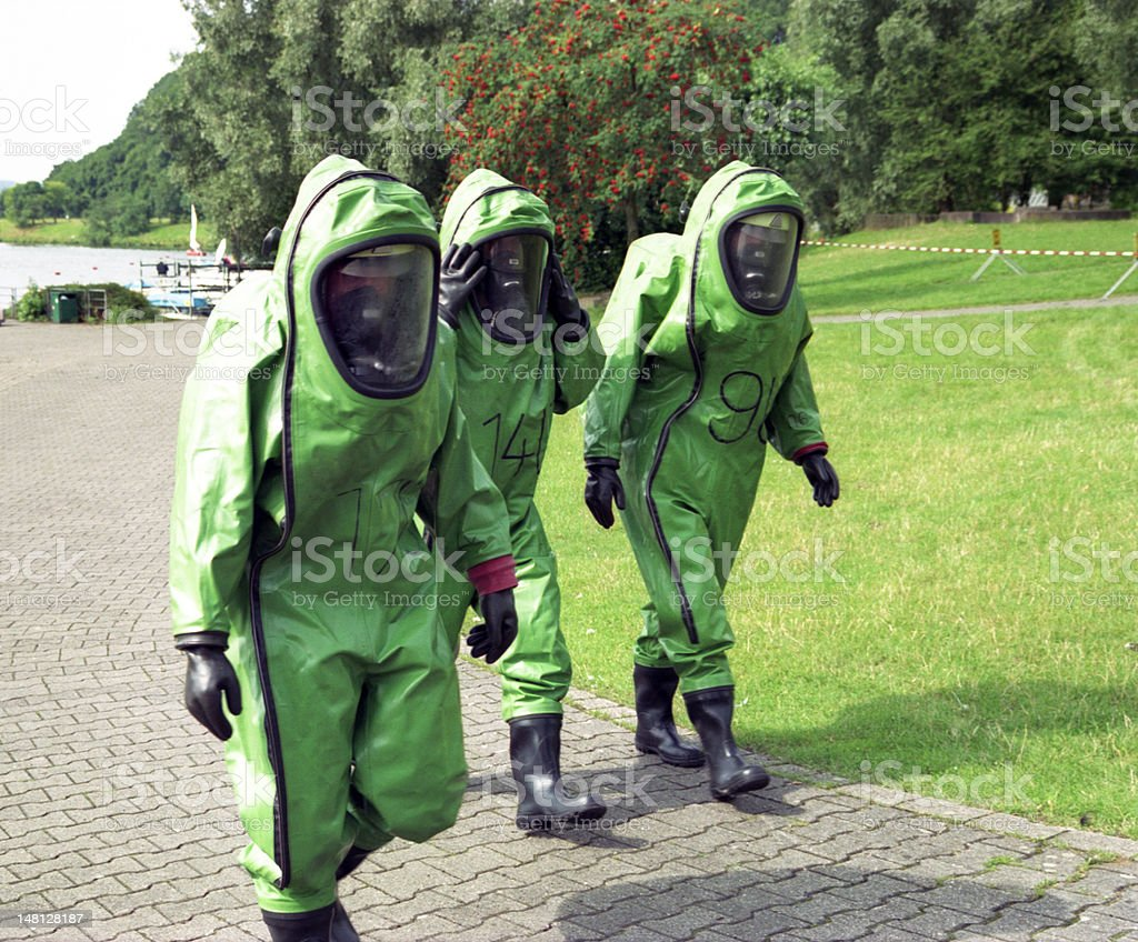 A picture of 3 people wearing protective suits stock photo