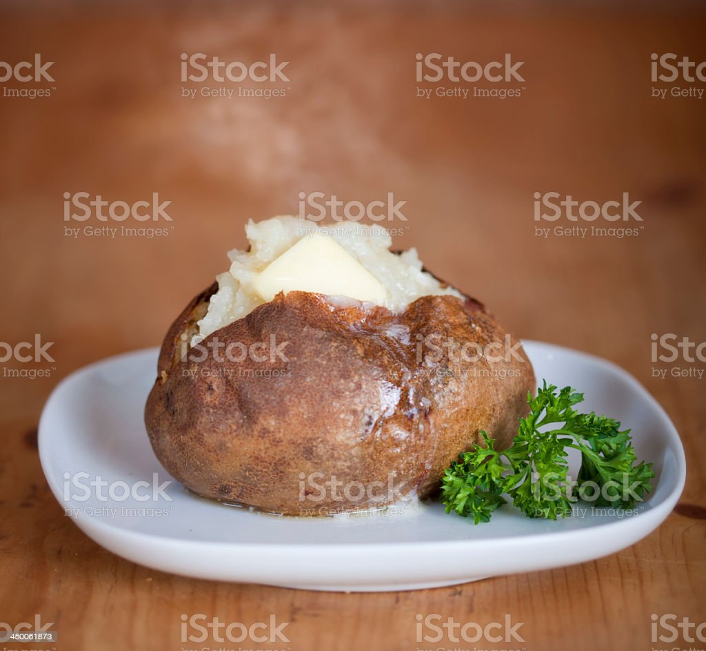A picture of a baked potato on a white plane stock photo