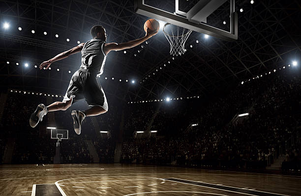 A picture of a basketball player dunking Close up image of professional basketball player about to do slam dunk during basketball game in floodlight basketball court jump shot stock pictures, royalty-free photos & images