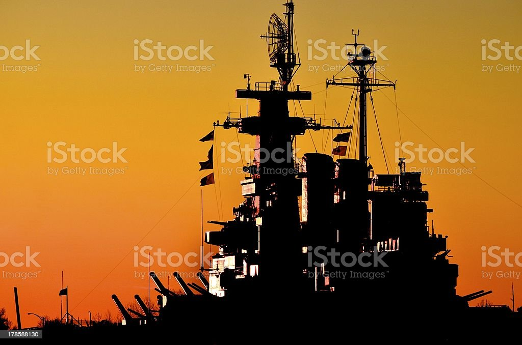 A picture of a battleship at sunset stock photo