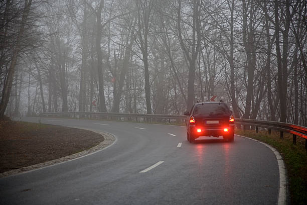 picture of a car on the road on a gray day - mist donker auto stockfoto's en -beelden