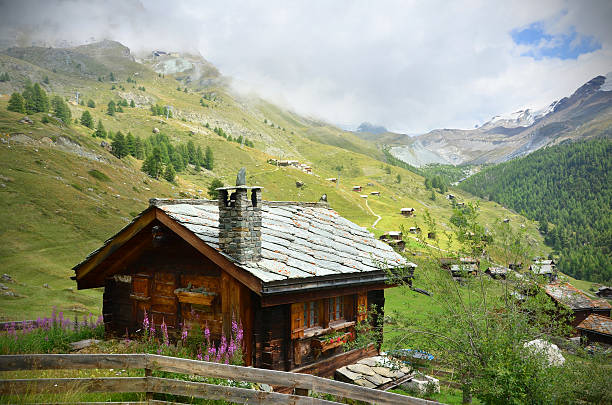 Picture of a chalet near Zermatt, Swaziland A traditional wooden Swiss chalet with a stone roof sits beside a hiking trail overlooking a small village near Zermatt. chalet stock pictures, royalty-free photos & images