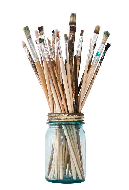 Picture of a clear jar filled with paint brushes Art brushes in an old jar with a clipping path paintbrush stock pictures, royalty-free photos & images