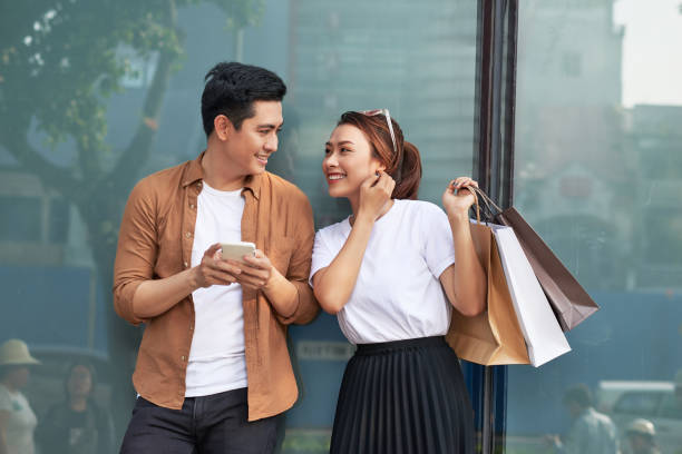 A picture of a couple shopping with smartphone in the city A picture of a couple shopping with smartphone in the city shopping couple asian stock pictures, royalty-free photos & images