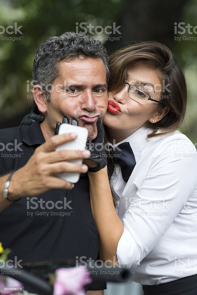 picture of a couple taking a self picture with his phone stock photo