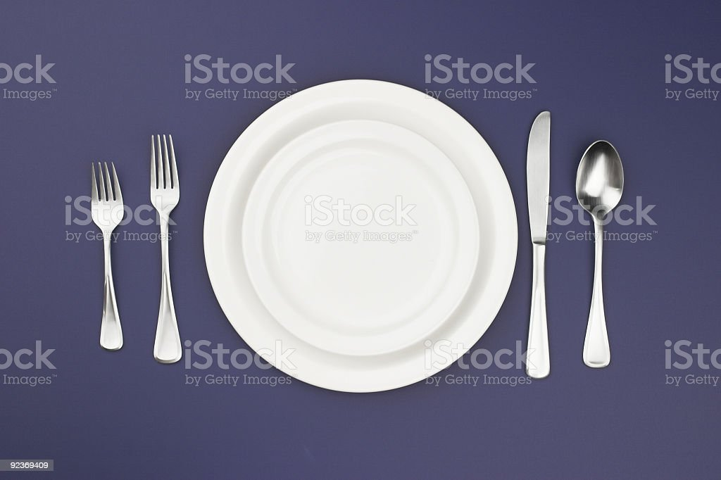 A picture of a dinner plate setting with a white plate royalty-free stock photo