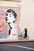 'Hollywood, California, USA - October 29, 2012: A bicycle wielding photographer aims and captures an image of a likeness to actress Audrey Hepburn.'