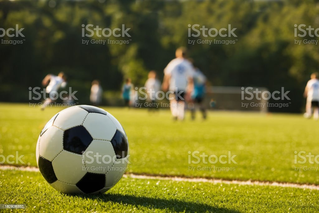 Picture of a football with kids playing in the background stock photo