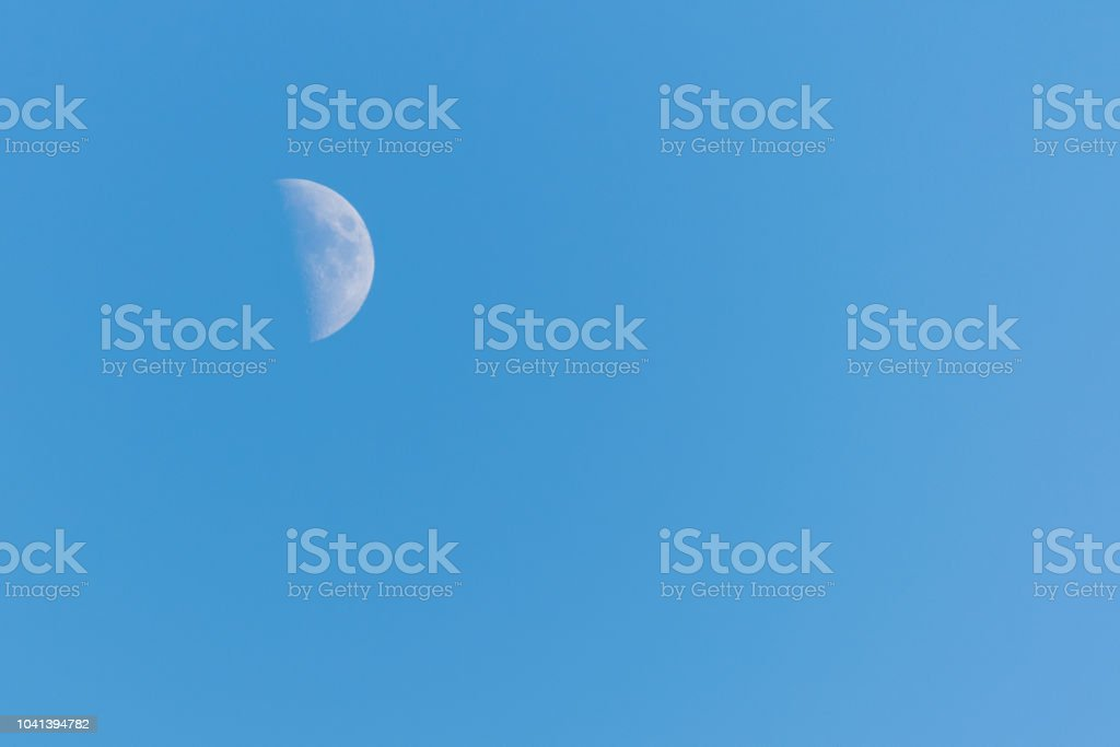 Picture of a half moon on a clear blue sky top left