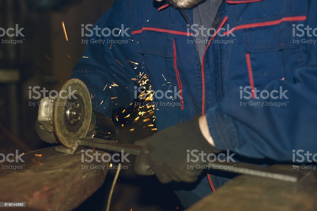 Picture of a hands of a worker while grinding metal stock photo