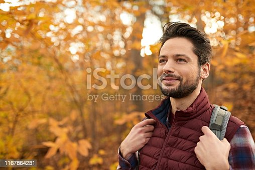 Portait of an attractive millennial man walking in autumn nature with backpack and trekking on a path surrounded by orange leaves