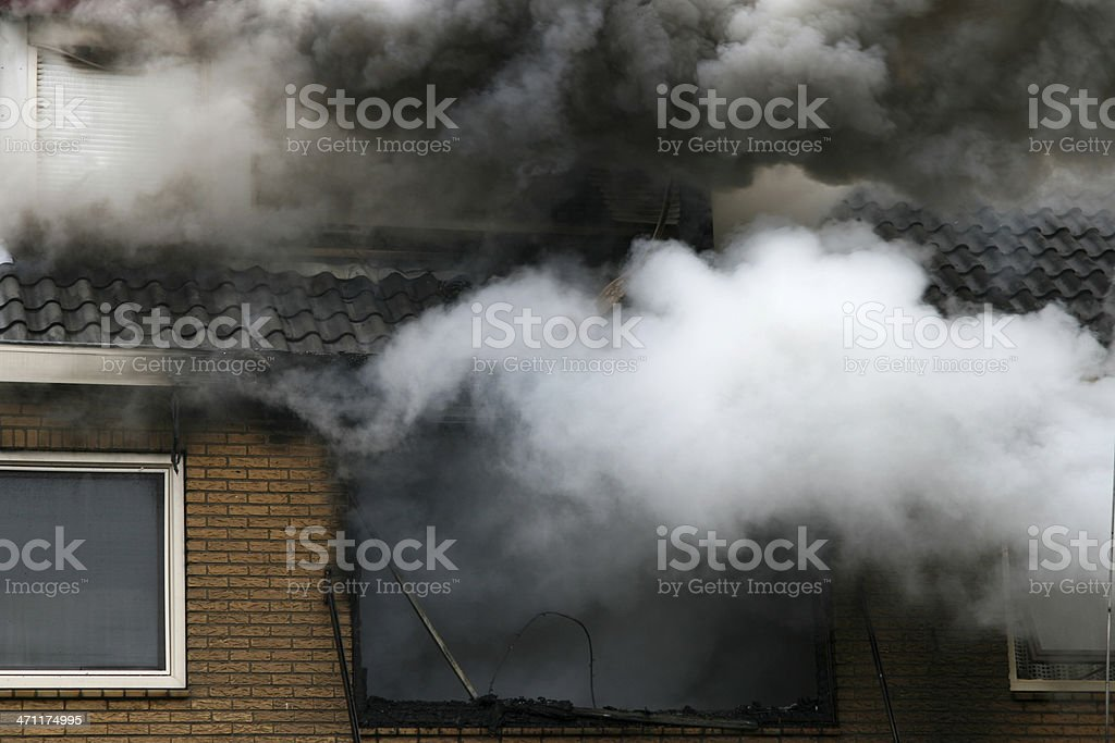 Picture of a house consumed in smoke and fire stock photo