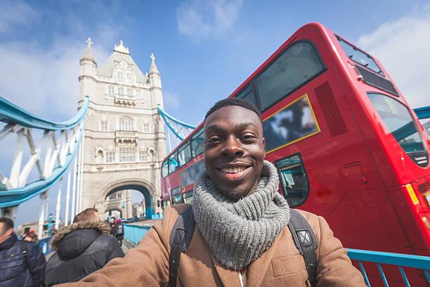 mann nehmen selfie mit in london tower bridge im hintergrund - englandreise stock-fotos und bilder
