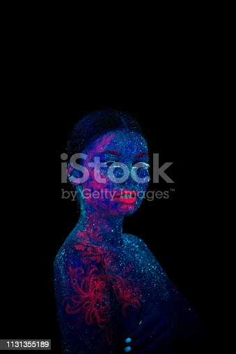 Picture of a pink jellyfish on the shoulder and face. Blue skin. Tilted her head to the shoulder, ultraviolet makeup. Looking at camera