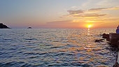 Picture of a sunset in Rovinj with sunball on the horizon in summer