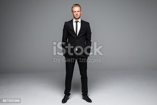 istock Picture of a young business man looking up while holding both hands in his pocket. 857350366