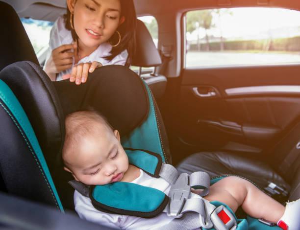 image d'une mère asiatique observant son fils dormant sur le siège d'auto, foyer sur le visage de garçon. - child car sleep photos et images de collection