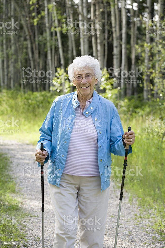 A picture of an older woman walking in the woods stock photo