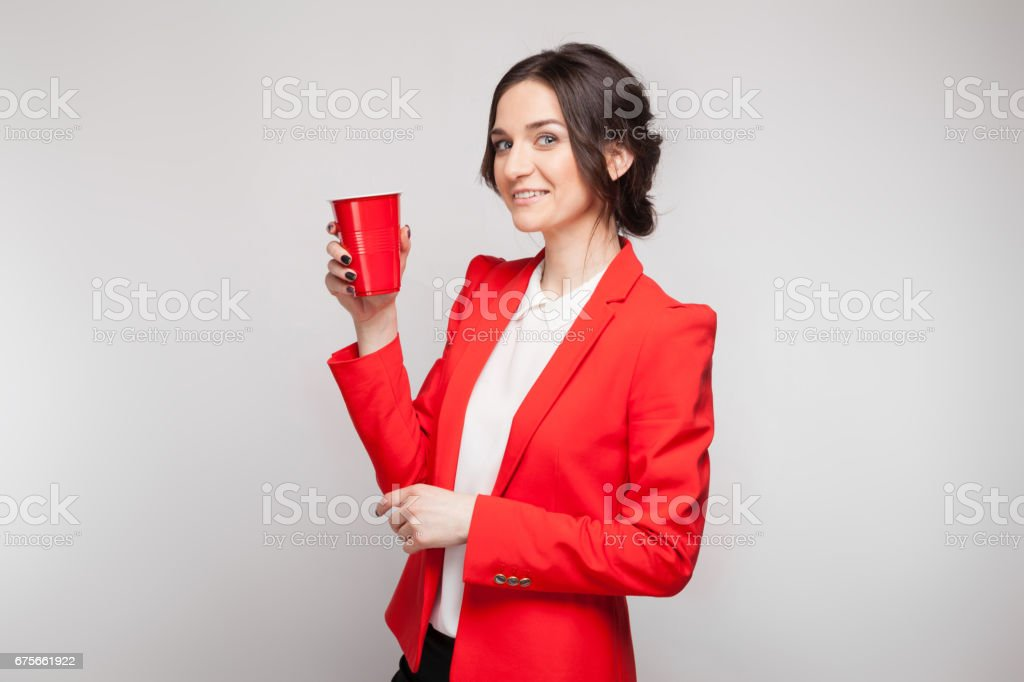 Picture of attractive woman in red dress with cup of beer in hands royalty-free stock photo