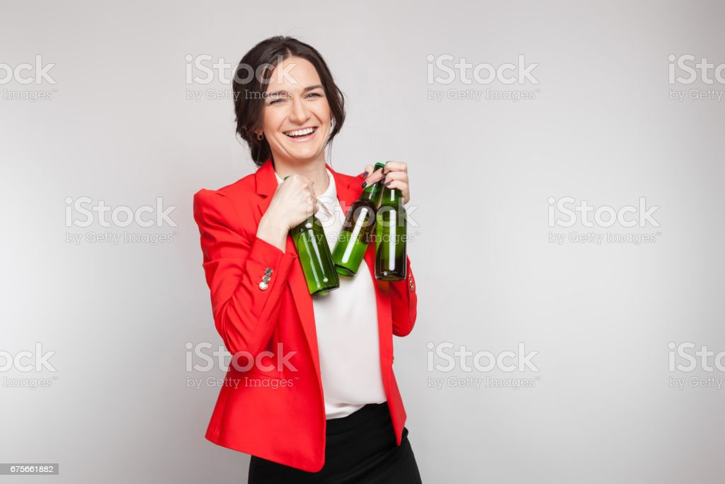 Picture of attractive woman in red dress with green beer in hands royalty-free stock photo