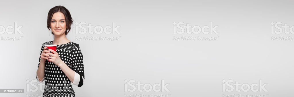Picture of attractive woman in speckled clothes standing with cup in hands royalty-free stock photo