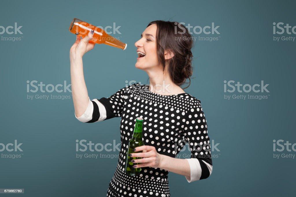 Soda ve elinde bira ile ayakta benekli giysili çekici kadın resim stok fotoğrafı