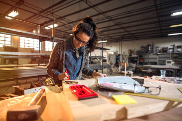 Picture of beautiful focused middle aged woman architect in her workshop working on new projects. Picture of beautiful focused middle aged woman architect in her workshop working on new projects. starting line stock pictures, royalty-free photos & images