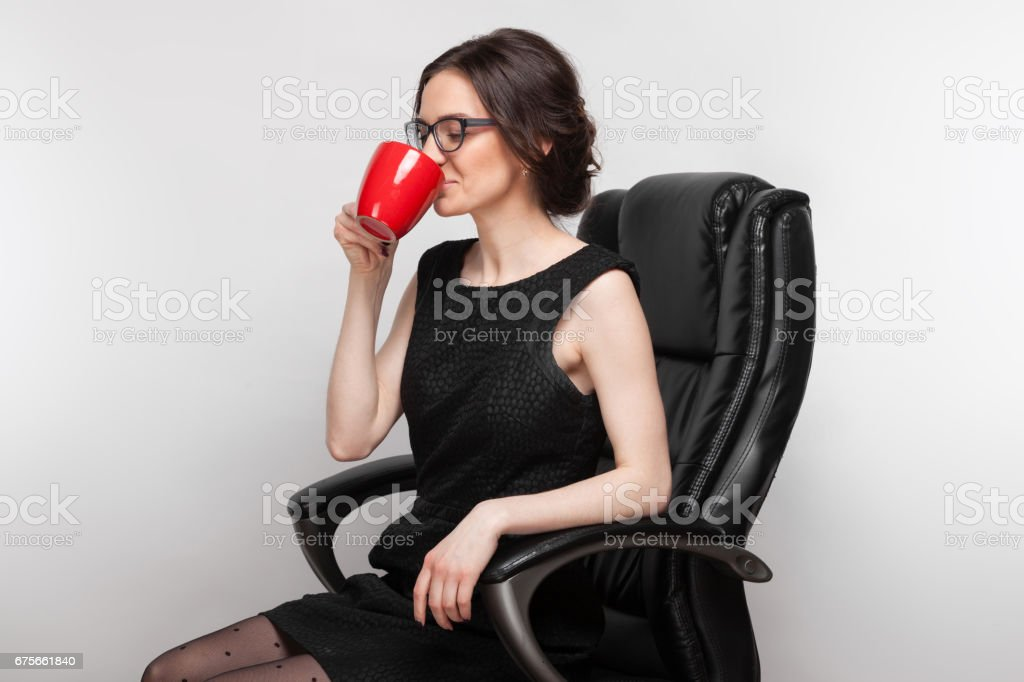 Picture of beautiful woman in black dress sitting in the armchair with coffe in hands royalty-free stock photo